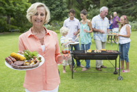 Portrait of smiling senior woman holding plate of barbecue and wine with family in background 11080008302| 写真素材・ストックフォト・画像・イラスト素材|アマナイメージズ