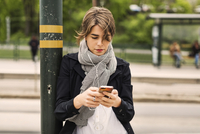 Young woman using mobile phone while listening to music through headphones at tram station 11081007657| 写真素材・ストックフォト・画像・イラスト素材|アマナイメージズ