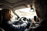 Smiling senior woman driving car while sitting by man taking selfie through smart phone 11081011224| 写真素材・ストックフォト・画像・イラスト素材|アマナイメージズ