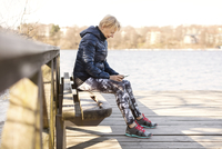 Senior woman in sportswear using phone while sitting on bench by lake 11081011236| 写真素材・ストックフォト・画像・イラスト素材|アマナイメージズ