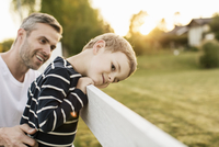 Father looking at smiling boy leaning on fence by grassy field 11081011311| 写真素材・ストックフォト・画像・イラスト素材|アマナイメージズ