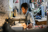 Serious male owner sewing fabric at shop 11081011399| 写真素材・ストックフォト・画像・イラスト素材|アマナイメージズ