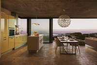Modern kitchen and dining room overlooking ocean at sunset 11086008951| 写真素材・ストックフォト・画像・イラスト素材|アマナイメージズ
