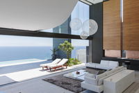 Living room and patio of modern house overlooking ocean 11086012318| 写真素材・ストックフォト・画像・イラスト素材|アマナイメージズ