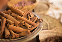 Cinnamon sticks on plate and other spices in background in spice market 11086019673| 写真素材・ストックフォト・画像・イラスト素材|アマナイメージズ