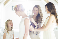 Matron of honor and bridesmaid helping bride with dressing in domestic room 11086020762| 写真素材・ストックフォト・画像・イラスト素材|アマナイメージズ