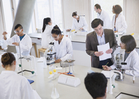 Science professor and college students using microscopes in science laboratory classroom 11086029673| 写真素材・ストックフォト・画像・イラスト素材|アマナイメージズ