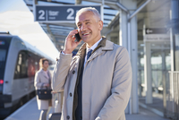 Smiling businessman talking on cell phone outside airport 11086030008| 写真素材・ストックフォト・画像・イラスト素材|アマナイメージズ