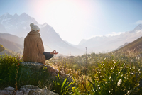 Young woman meditating on rock in sunny, remote valley 11086032394| 写真素材・ストックフォト・画像・イラスト素材|アマナイメージズ