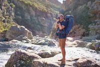 Young man with backpack hiking, photographing with camera on sunny rocks 11086032401| 写真素材・ストックフォト・画像・イラスト素材|アマナイメージズ