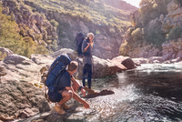 Young couple with backpacks hiking, splashing water at stream 11086032425| 写真素材・ストックフォト・画像・イラスト素材|アマナイメージズ