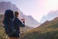 Young man with backpack using camera phone in sunny valley below mountains 11086032454| 写真素材・ストックフォト・画像・イラスト素材|アマナイメージズ