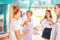 Senior female business owner serving ice cream to young women at food cart 11086032634| 写真素材・ストックフォト・画像・イラスト素材|アマナイメージズ