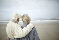 Pensive senior couple hugging and looking at ocean view on windy winter beach 11086032718| 写真素材・ストックフォト・画像・イラスト素材|アマナイメージズ