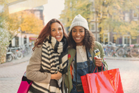 Portrait smiling young women with shopping bags on urban autumn street 11086033458| 写真素材・ストックフォト・画像・イラスト素材|アマナイメージズ