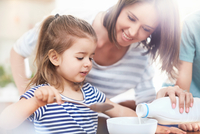 Daughter watching mother pouring milk into cereal bowl 11086033763| 写真素材・ストックフォト・画像・イラスト素材|アマナイメージズ