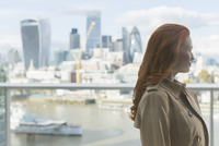 Pensive businesswoman with red hair looking at urban city view from balcony, London, UK 11086033917| 写真素材・ストックフォト・画像・イラスト素材|アマナイメージズ