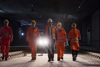 Male foreman and construction workers walking in dark construction site underground 11086034101| 写真素材・ストックフォト・画像・イラスト素材|アマナイメージズ
