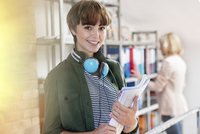 Portrait smiling female design professional with headphones holding paperwork in design library 11086034390| 写真素材・ストックフォト・画像・イラスト素材|アマナイメージズ