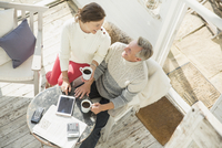 View from above mature couple drinking coffee and using digital tablet on sun porch 11086035339| 写真素材・ストックフォト・画像・イラスト素材|アマナイメージズ