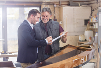 Male customer signing paperwork for finished wood kayak in workshop 11086035377| 写真素材・ストックフォト・画像・イラスト素材|アマナイメージズ