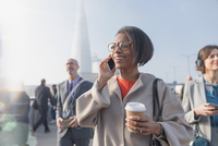 Smiling businesswoman drinking coffee and talking on cell phone on sunny busy urban pedestrian bridge 11086035519| 写真素材・ストックフォト・画像・イラスト素材|アマナイメージズ