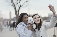 Playful, smiling lesbian couple with white dog taking selfie with camera phone in urban park, London, UK 11086035609| 写真素材・ストックフォト・画像・イラスト素材|アマナイメージズ