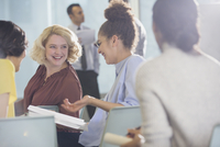 Smiling businesswomen discussing paperwork in conference audience 11086035640| 写真素材・ストックフォト・画像・イラスト素材|アマナイメージズ