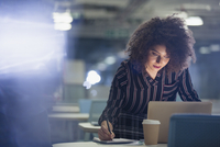 Focused businesswoman working late at laptop, taking notes in dark office 11086035752| 写真素材・ストックフォト・画像・イラスト素材|アマナイメージズ