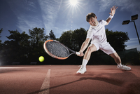 Young man playing tennis, reaching with tennis racket on clay court 11086035778| 写真素材・ストックフォト・画像・イラスト素材|アマナイメージズ