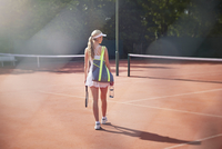 Young female tennis player walking with tennis racket, bag and water bottle on sunny clay tennis court 11086035781| 写真素材・ストックフォト・画像・イラスト素材|アマナイメージズ