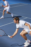 Determined young male tennis doubles players poised with tennis rackets on tennis court 11086035785| 写真素材・ストックフォト・画像・イラスト素材|アマナイメージズ