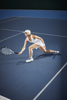 Young female tennis player playing tennis, reaching with tennis racket on blue tennis court 11086035791| 写真素材・ストックフォト・画像・イラスト素材|アマナイメージズ