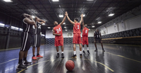Young male basketball players high-fiving, celebrating on court in gymnasium 11086035870| 写真素材・ストックフォト・画像・イラスト素材|アマナイメージズ