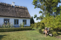 Denmark, Mon, Woman sitting in front of house and reading 11090020264| 写真素材・ストックフォト・画像・イラスト素材|アマナイメージズ