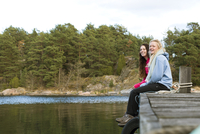 Sweden, Sodermanland, Braviken, Teenage girl (16-17) sitting with young woman on jetty 11090020665| 写真素材・ストックフォト・画像・イラスト素材|アマナイメージズ