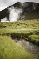 Iceland, Sudurland, Hveragerdi, Reykjadalur, Woman bathing in stream with geyser and mountain in background 11090020818| 写真素材・ストックフォト・画像・イラスト素材|アマナイメージズ