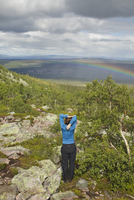 Sweden, Dalarna, Fulufjallet, Man standing on hill and looking at landscape with rainbow 11090020946| 写真素材・ストックフォト・画像・イラスト素材|アマナイメージズ