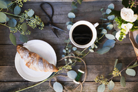 Sweden, Coffee cup, croissant and flowers on wooden table 11090021873| 写真素材・ストックフォト・画像・イラスト素材|アマナイメージズ