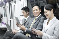 Business persons using digital products in subway train 11091002465| 写真素材・ストックフォト・画像・イラスト素材|アマナイメージズ