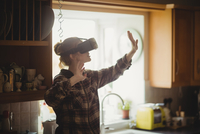 Woman experiencing virtual reality headset in kitchen 11092003415| 写真素材・ストックフォト・画像・イラスト素材|アマナイメージズ