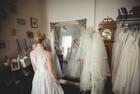 Young bride in a white dress looking into mirror 11092005774| 写真素材・ストックフォト・画像・イラスト素材|アマナイメージズ