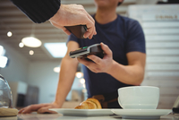 Customer making contactless payment in coffee shop 11092005919| 写真素材・ストックフォト・画像・イラスト素材|アマナイメージズ