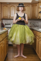 A woman wearing a lime green ballet tutu, standing in a ballet position in her kitchen. 11093002895| 写真素材・ストックフォト・画像・イラスト素材|アマナイメージズ