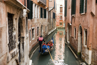 A gondola boat gliding down a small narrow waterway, between historic houses in the city of Venice.  11093004988| 写真素材・ストックフォト・画像・イラスト素材|アマナイメージズ