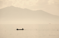 Two people in a small fishing boat on a lake drawing in nets. Mountains in the background.  11093005173| 写真素材・ストックフォト・画像・イラスト素材|アマナイメージズ