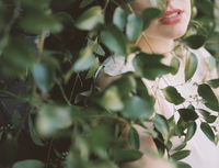 A blonde haired woman in a dress leaning against a wall with a growing vine. 11093005335| 写真素材・ストックフォト・画像・イラスト素材|アマナイメージズ