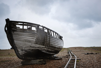 Abandoned wooden boat beached on the shingle near old narrow gauge rails.  11093006335| 写真素材・ストックフォト・画像・イラスト素材|アマナイメージズ