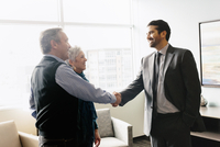 A man greeting a mature couple in an office.  11093009667| 写真素材・ストックフォト・画像・イラスト素材|アマナイメージズ