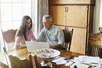 Senior couple sitting at a dining table, using a laptop computer, paperwork and bills on the table. 11093010854| 写真素材・ストックフォト・画像・イラスト素材|アマナイメージズ